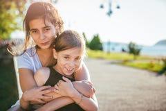 Dos muchachas que sonríen junto en un parque Imagen de archivo libre de regalías