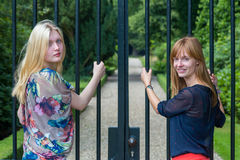Dos muchachas que sostienen las barras de metal de la puerta de la entrada Imagenes de archivo