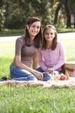 Dos muchachas que tienen comida campestre en parque fotos de archivo
