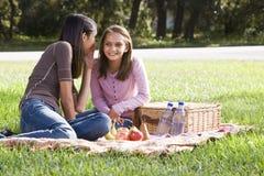 Dos muchachas que tienen comida campestre en parque Fotos de archivo libres de regalías
