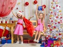 Dos muchachas que tienen la diversión y Felices Año Nuevo de regalos en una atmósfera hogareña del Año Nuevo Imagenes de archivo