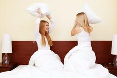 Dos muchachas que tienen una lucha de almohada en dormitorio Fotos de archivo