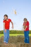 Dos muchachas que tienen una lucha del heno. Fotografía de archivo libre de regalías