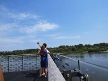Dos muchachas que tiran a Selfie representan mientras que se colocan en una plataforma de visión sobre el río Vistula en Varsovia fotos de archivo