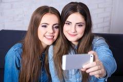 Dos muchachas que toman la foto del selfie con el teléfono elegante foto de archivo