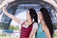 Dos muchachas que toman las fotos en la torre Eiffel Imagen de archivo libre de regalías
