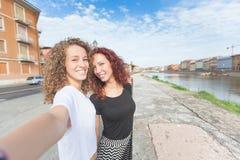 Dos muchachas que toman un selfie en la ciudad Foto de archivo