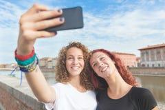 Dos muchachas que toman un selfie en la ciudad Foto de archivo libre de regalías