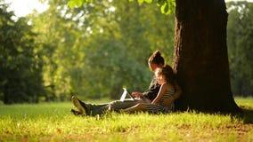 Dos muchachas que usan la tableta en un parque hermoso, un día de verano caliente almacen de metraje de vídeo