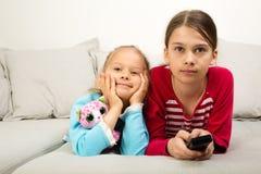 Dos muchachas que ven la TV fotos de archivo