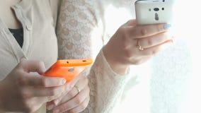 Dos muchachas que ven las fotos usando los teléfonos móviles metrajes