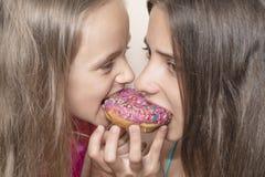 Dos muchachas quieren comer los anillos de espuma dulces Las muchachas miran con un apetito los anillos de espuma coloridos imágenes de archivo libres de regalías