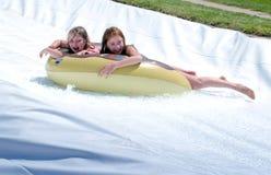 Dos muchachas ríen mientras que se deslizan abajo de un waterslide Foto de archivo libre de regalías