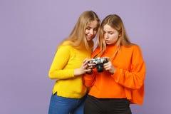 Dos muchachas rubias bastante jovenes de las hermanas de los gemelos en la ropa colorida viva que sostiene la cámara retra de la  fotos de archivo libres de regalías