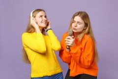 Dos muchachas rubias bonitas de las hermanas de los gemelos en ropa colorida escuchan música con los auriculares, cantan la canci imagen de archivo libre de regalías