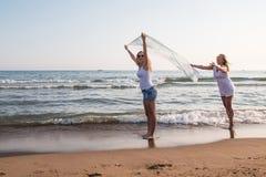 Dos muchachas rubias en la playa cerca del mar Imagen de archivo