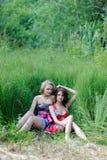 Dos muchachas rubias jovenes y la mujer morena en los vestidos brillantes que presentan en verano parquean en hierba alta Imagenes de archivo