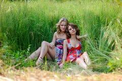Dos muchachas rubias jovenes y la mujer morena en los vestidos brillantes que presentan en verano parquean en hierba alta Foto de archivo