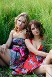 Dos muchachas rubias jovenes y la mujer morena en los vestidos brillantes que presentan en verano parquean en hierba alta Imagen de archivo libre de regalías
