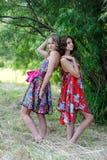 Dos muchachas rubias jovenes y una mujer morena en los vestidos brillantes que presentan en un verano parquean contra un contexto Imágenes de archivo libres de regalías