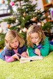 Dos muchachas rubias que leen un libro delante del árbol de navidad Imagen de archivo
