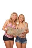 Dos muchachas rubias que llevan pantalones cortos de los vaqueros con el mapa Foto de archivo