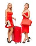 Dos muchachas rubias que llevan rojo se visten con la maleta y el bolso grandes imagenes de archivo