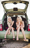 Dos muchachas rubias que se sientan en tronco del coche quebrado Foto de archivo libre de regalías