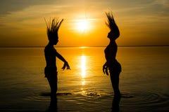 Dos muchachas sacuden su pelo mojado en la playa en el fondo de la puesta del sol Foto de archivo libre de regalías