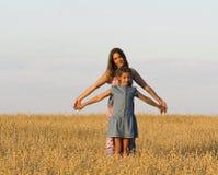 Dos muchachas se están colocando en un campo Imágenes de archivo libres de regalías