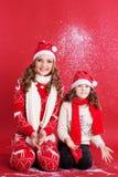 Dos muchachas se están divirtiendo con nieve falsa Imagen de archivo libre de regalías