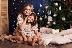 Dos muchachas se están sentando cerca del árbol de navidad en casa Imagenes de archivo