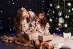 Dos muchachas se están sentando cerca del árbol de navidad en casa Foto de archivo libre de regalías