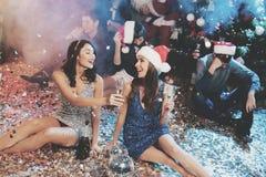Dos muchachas se están sentando en el piso Alrededor de ellos es el confeti dispersado Descansan después del partido por el Año N Foto de archivo libre de regalías
