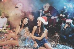 Dos muchachas se están sentando en el piso Alrededor de ellos es el confeti dispersado Descansan después del partido por el Año N Fotografía de archivo