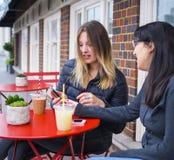 Dos muchachas se relajan en un café de la calle y tienen una bebida Imagenes de archivo