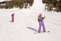 Dos muchachas se sientan en las cuestas del esquí Fotografía de archivo