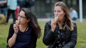 Dos muchachas se sientan en los prados en un parque y comen el helado almacen de video