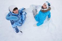 Dos muchachas se sientan en nieve y la preparación montar Fotografía de archivo