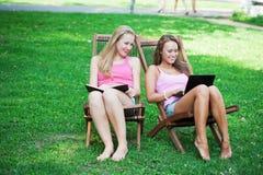 Dos muchachas se sientan en salones de la calesa fotos de archivo