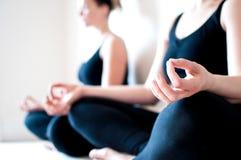 Dos muchachas sientan Legged cruzado en una actitud de la yoga Imagenes de archivo