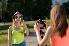 Dos muchachas son estudiantes En verano en ciudad Vestido en ropa brillante fotografiado en naturaleza Vlog y blog de registro Fotos de archivo
