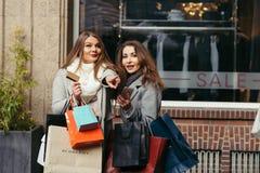 Dos muchachas son felices con una tarjeta de crédito delante de la demostración-ventana Imágenes de archivo libres de regalías