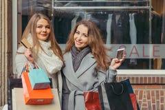 Dos muchachas son felices con una tarjeta de crédito delante de la demostración-ventana con la venta escrita en ella Foto de archivo