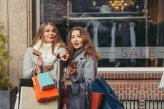 Dos muchachas son felices con una tarjeta de crédito delante de los wi del showwindow Imágenes de archivo libres de regalías