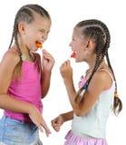 Dos muchachas sonrientes con el caramelo. Foto de archivo