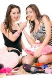 Dos muchachas sonrientes con el caramelo. Aislado Foto de archivo