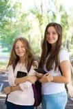 Dos muchachas sonrientes con las tabletas Imágenes de archivo libres de regalías