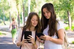 Dos muchachas sonrientes con las tabletas Imagen de archivo