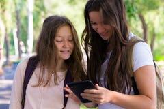 Dos muchachas sonrientes con las tabletas Fotos de archivo